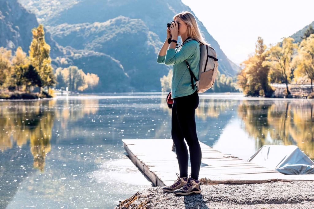Solo woman traveler outdoor taking a picture with the EVF viewfinder