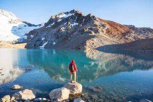 Man Back with backpack facing lake with hills