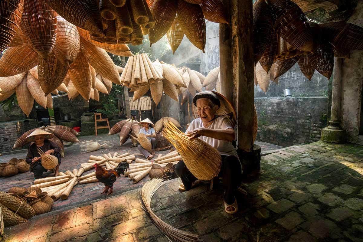 Vietnamese girl making a leaf hat